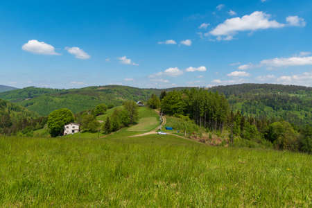 Beuatiful Slezske Beskydy mountains near Filipka hill in Czech republic with meadow, few isolated houses, dirt roads and hills on the background during springtime day