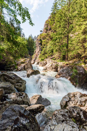 Wild Varinka river with cascades, big stones and rocks on the background in lower parf of Vratna dolina valley in Mala Fatra mountains near Terchova village in Slovakia