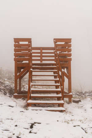 small wooden view tower on Velka steibrna hill in Zlatohorska vrchovina mountains on czech - polish border during cloudy winter day