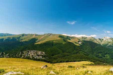 Beautiful scenery of Godeanu and Retazatul Mic mountains from meadow bellow Osleva hill in Valcan mountains in Romania