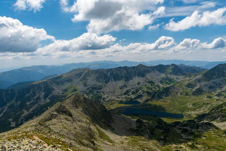 Retezat mountains with peaks and Bucura lakes from Peleaga mountain peak in Romania during beuatiful summer afternoon