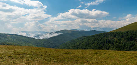 Valcan mountains in Romania during summer afternoon with blue sky and clouds