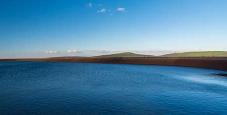 Dlouhe strane water reservoir with Praded, Petrovy kameny and Vysoka hole hill in Jeseniky mountains in Czech republic during summer evening