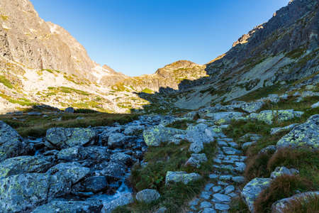 Velicka dolina valley with stone hiking trail, stones, peska around and clear sky in Vysoke Tatry mountains in Slovakia