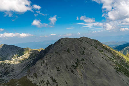 Varful Papusa with few other peaks from Varful Peleaga mountain peak in Retezat mountains in Romania during beuatiful summer day