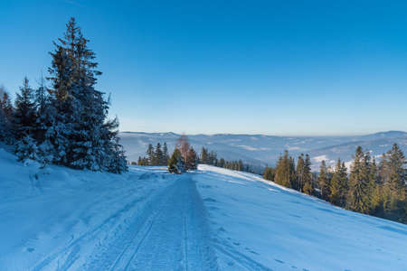 Snow covered road with hills on the backgroiund and clear sky on Cienkow mountain ridge in Beskid Slaski mountains in Poland during freezing winter morning