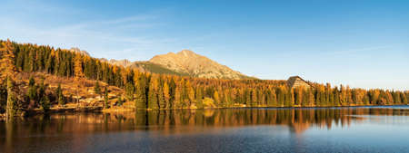 Strbske pleso lake with peaks on the background and colorful trees in autumn Vysoke Tatry mountains in Slovakia