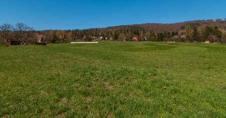 Meadow with cottages around, forest covered hills and clear sky in Slezske Beskydy mountains in Czech republic during springtime