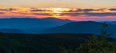 Sunset with hills, colorful sky and clouds from Dlouhe strane hill in summer Jeseniky mountains in Czech republic