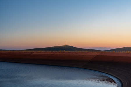 Praded hill and Petrovy kameny rock formation from Dlouhe strane hill with water reservoir in Jeseniky mountains in Czech republic during summer sunset with clear sky