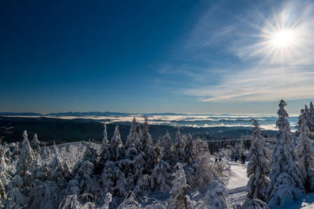 Amazing view from Lysa hora hill in winter Moravskoslezske Beskydy mountains in Czech republic with many hills, mist in valleys and clear sky