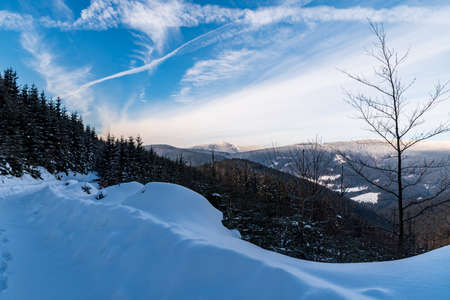 Lysa hora and Travny hills from forest road bellow Misaci hill summit above Moravka village in winter Moravskoslezske Beskydy mountains in Czech republic