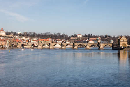 Vltava river with Charles Bridge in Prague city in Czech republi during late autumn morning with blue sky