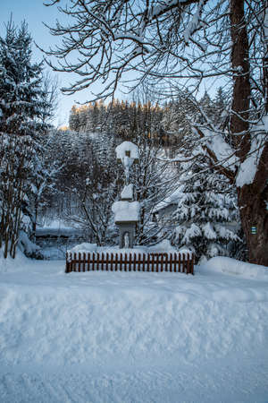 Cruxifix in winter landscape with snow, trees and clear sky on Bebek above Moravka village in Moravskoslezske Beskydy mountains in Czech republic