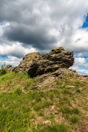 Smaller rock formation on Sokol hill in Jeseniky mountains in Czech republic during summer afternoon with blue sky and clouds Reklamní fotografie