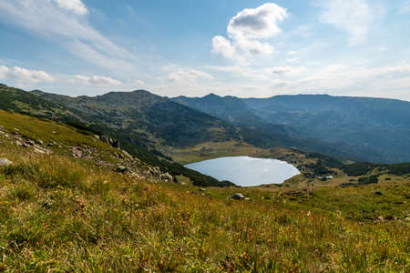 Retezat mountains with peaks and Zanoaga lake in Romania during beautiful summer day