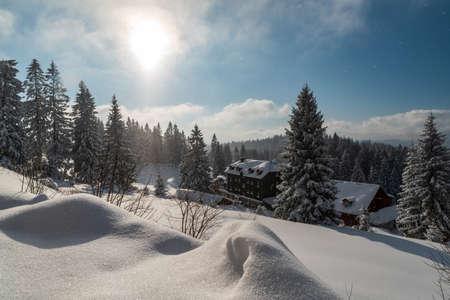Winter on Bily kriz in Moravskoslezske Beskydy mountains on czech - slovakian borders with few buildings, snow and trees