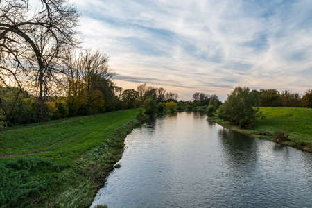 Olse river with trees and grass around from Most Sokolovskych hrdinz bridge in Karvina city in Czech republic during beautiful autumn day