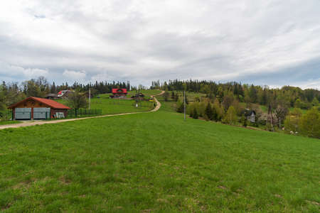 Ceslar hill in Slezske Beskydy mountains on czech - polish borders with meadow, few houses and trees during springtime Reklamní fotografie