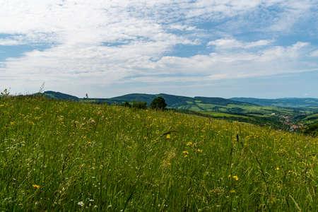 Beautiful scenery of Bile Karpaty mountains near Laz hill summit above Nedasova Lhota village in Czech republic with flowering meadow, hills and Nedasova Lhota village