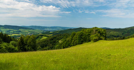 Hilly landscape with meadows, few villages, forest, hills and blue sky with clouds - view from meadows above Nedasova Lhota village in Bile Karpaty mountains in Czech republic near borders with Slovakia