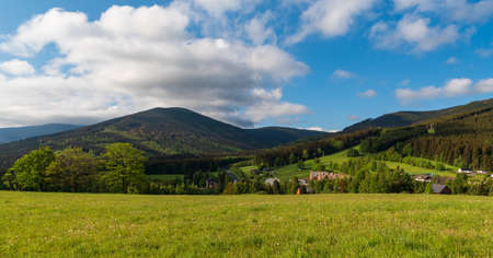 Filipovice settlement with hills around from Brst hill covered by meadow in springtime Jeseniky mountains in Czech republic