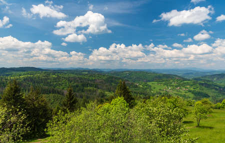 Beuatiful view from view tower on Martacky vrch hill in Javorniky mountains in Slovakia with many hills and blue sky with clouds