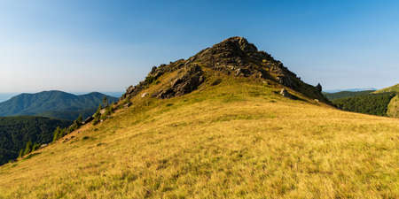 hill covered by meadow with rock formation on summit and other hills on the background - Oslea mountain ridge in Valcan mountains in Romania Reklamní fotografie