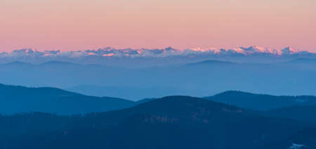 View to snowcapped peaks of Tatra mountains from Lysa hora hill in Moravskoslezske Beskydy mountains in Czech republic during late autumn sunset