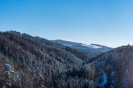 Winter Rychlebske hory mountains from Rychleby castle ruins in Czech republic with hills covered by forest and few forest glades