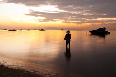 sanur: traditional Balinese fisherman fishing on beach on Sanur beach at sunrise, Bali, Indonesia