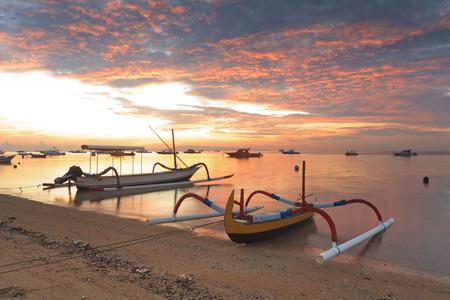 伝統的なバリ式船ジュクン (船近くを) サヌールのビーチに日の出、バリ、インドネシア