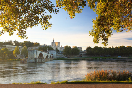 Avignon Bridge with Popes Palace and Rhone river at sunrise framed with sunny trees, Pont Saint-Benezet, Provence, France