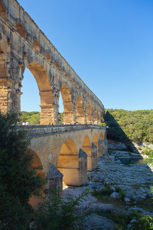 garde: Pont du Gard is an old Roman aqueduct near Nimes in Southern France, bridge over river Garde on sunny day wit blue sky,