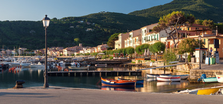 capraia: Panorama of Marciana Marina harbour with Monte Cappane mountain in backround, rocks and yacht in bay on island Elba, Tuscany, Italy, Europe Stock Photo