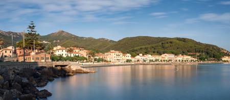 capraia: Panorama of Marciana Marina promenade with Monte Cappane mountain in backround, rocks and yacht in bay on island Elba, Tuscany, Italy, Europe Stock Photo
