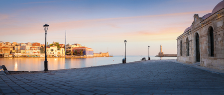 Panorama of Old harbor of Chania with the lighthouse, bench and lamp with beautiful sky at sunrise, Crete, Greece