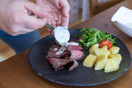 Delicious succulent rare roast beef steak sliced and served with potatoes and fresh vegetables on stone plate
