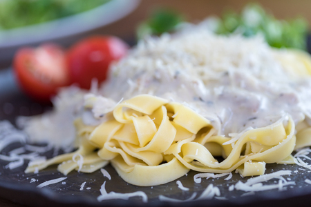 Pasta with cheese sauce on dark plate