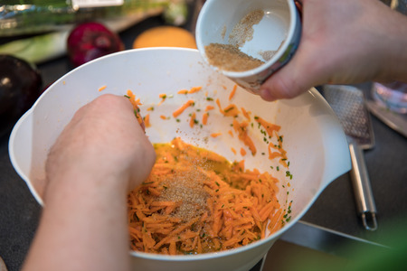 Carrot salad preparation with hand in white bowl Imagens