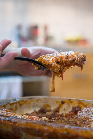 Man serving Lasagna with beef ragout sauce or Lasagna bolognese with cheese at home environment