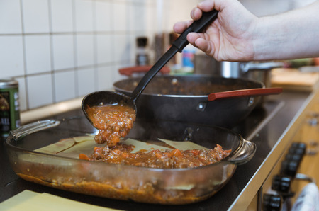Preparation Lasagna with beef ragout sauce or Lasagna bolognese with cheese on white plate and wooden background