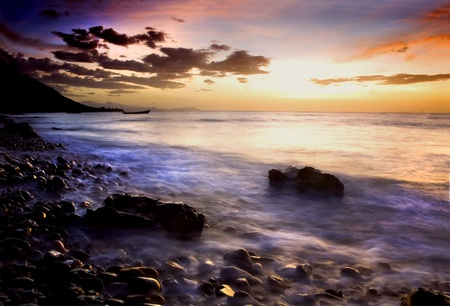 Picturesque sunset and cloudscape over rocky coastline with silhouetted boat in background, Socotra or Soqotra island in Indian ocean.  Stock Photo - 8907241
