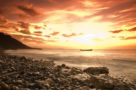 Dramatic sunset over the sea with fishingboat, socotra, yemen photo
