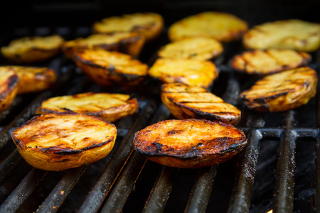 potatos: Slices of grilled potatos on a grill Stock Photo
