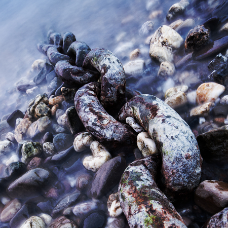 An old steel chain on a riverside