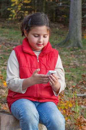 Cute kid, a girl, playing with a smart phone in forrest. Illustrative of influence of technology on kids and our lives. photo