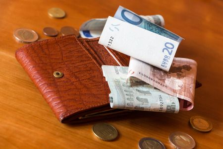 Wallet and some money scattered on a woden table photo