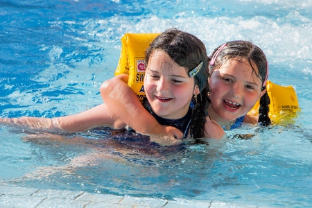 Two small kids, girls, cheerfully playing in a swimming pool. photo
