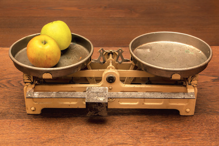 tarnished: Vintage kitchen scales on wooden table. Stock Photo